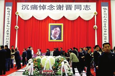 谢晋遗体告别仪式大厅庄严肃穆,以红色的帷幕为背景。