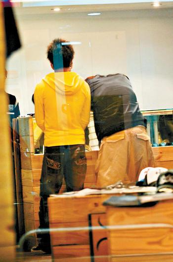 杨宗纬(右)与师弟(左)在东区服饰店内商量如何摆脱记者,杨更苦恼得整个人趴在柜台上