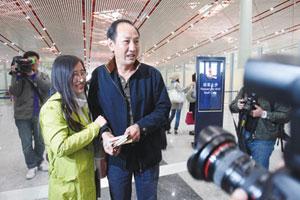 """在首都机场,刘翔""""调虎离山""""躲开记者,他的教练孙海平却被粉丝和记者们层层包围 摄/记者黑克制图/李铭"""