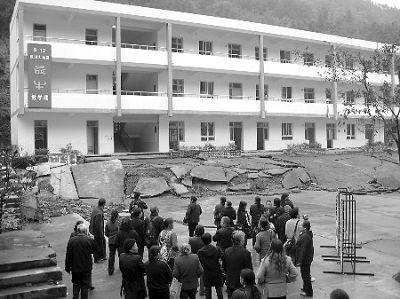 """一批游客正在汶川大地震中的""""最牛""""教学楼前参观。汶川大地震发生后,四川省彭州市白鹿镇一学校内的新建教学楼被整体抬高近3米,但楼体依然屹立原地不倒,当地有关部门将其开发成了景点。 CFP供图"""