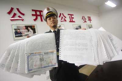 昨日,南岸,执法人员展示超限车被处罚的35张罚款单 记者 钟志兵