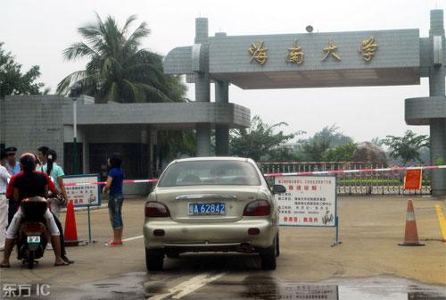 """2008年11月4日,海南大学东大门放置着""""因施工请谅解""""等告示牌,设警戒线和专门人员,阻止外来人员和车辆进入。"""