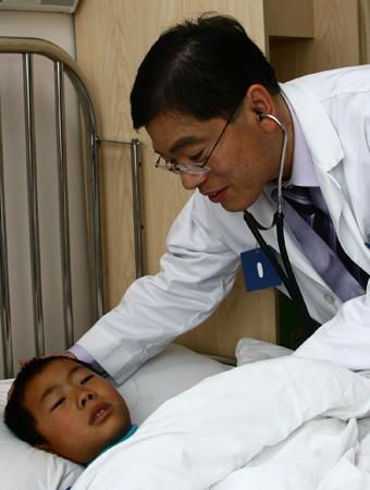 复旦大学附属儿科医院心血管中心主任贾兵教授在病房探视刚做完手术的6岁患儿张成政