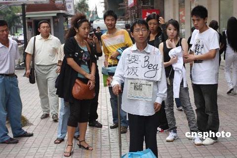 """9月9日,一名特别的""""乞丐""""在哈尔滨市南岗区果戈里大街乞讨。记者了解到,""""乞丐""""名叫夏海波,1982年9月15日出生,高二时因病辍学,治病花光了家里的钱,但是病还是没有医治好。2006年他离开家乡,试图找份工作养活自己,但因为自身残疾没有找到合适的工作。生活使他走上街头,试图靠乞讨的钱治病延缓病情发展。夏海波开了博客,将每天的感受记录在博客里。他在博客里公开了自己的银行帐号,以便接受网友的捐助。 中新社发 王忠言 摄"""