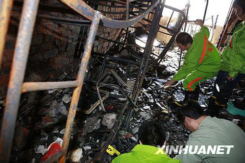 11月14日,消防人员正在清理火灾发生现场