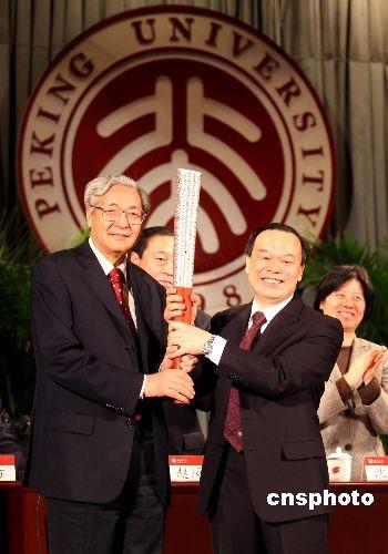 11月14日下午,周其凤(右)接替许智宏出任北京大学校长。卸任后的许智宏(左)将自己的奥运会火炬捐赠给北京大学,并亲手转交给自己的继任者周其凤。中新社发王天天 摄