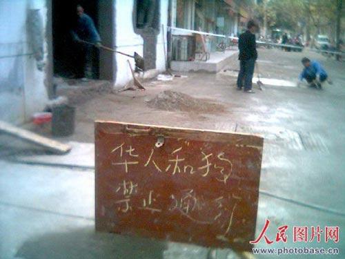 """商家为挡行人通过,挂出""""华人与狗禁止通行""""招牌,此行为受到市民的不解和指责。  版权作品,请勿转载。"""