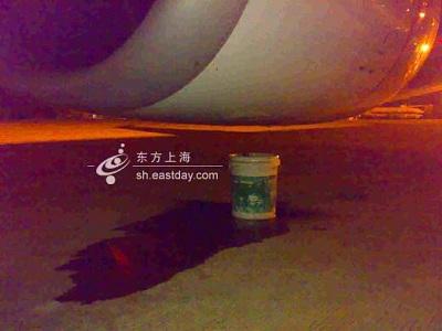 机组人员用桶在右机翼下侧接住不断滴下的机油。摄影:宣克炅