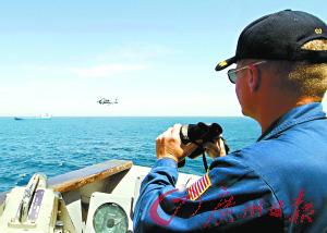 2008年9月30日,一名美国海军军官正在索马里海域监视远处一艘海盗船只。