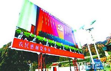 """平谷区大兴庄镇一村口,竖立着一块宣传""""土地流转第一拍""""的巨幅广告牌(资料图片)"""