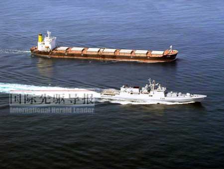 11月11日,印度军舰(下)在索马里海域保护印度货轮.法新社