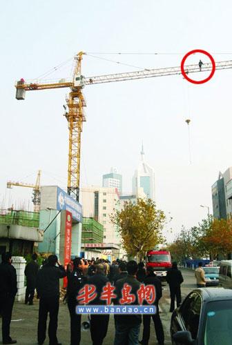 一名工人站在塔吊臂上讨债。