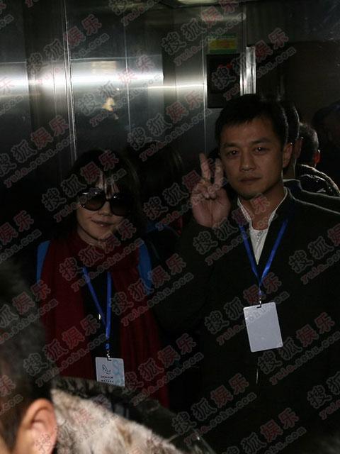图:鹏菲夫妇抵达宾馆 李亚鹏做V字手势