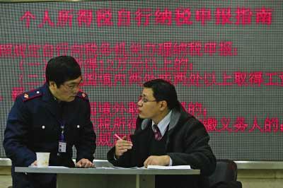 税务工作人员指导纳税人填写申报资料  记者 陈诚 摄