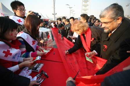 到场的嘉宾与现场人群一起在巨型红丝带上签名