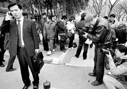 今天上午,周成宇(左一)打电话让家人把诉状送到法院,他旁边站满了记者
