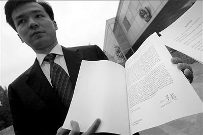 周成宇在展示黄静签名的起诉书。 本报记者董世彪摄