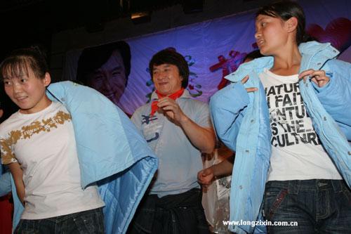 成龙亲自帮孤儿学校的学生把捐赠的棉衣穿上