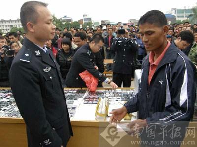 在一个摆满被盗手机的认领台前,一名失主从民警手中接过被盗的现金。