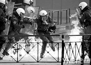 防暴警察躲避骚乱人群的汽油弹袭击