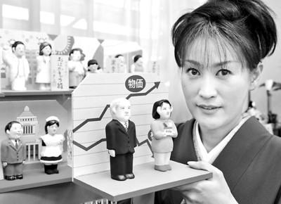 """日本一家玩具公司上周推出年度""""新闻娃娃"""",分别是美国总统布什和日本普通家庭主妇。在背后的图表上,上升的指数为物价,下降的为股价。"""