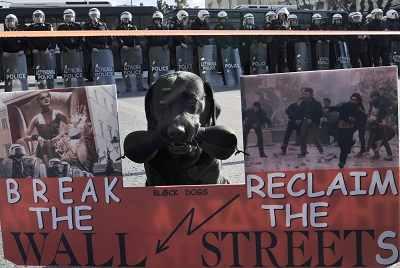 12月10日,雅典,在工会组织的游行中,一条狗叼着一块标牌站在警察组成的人墙前。新华/路透
