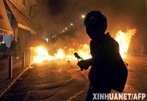 12月8日,一名示威者在希腊首都雅典的一个着火现场抗议。雅典市中心地区的骚乱爆发于6日晚,起因是警察打死一名15岁少年。目前骚乱仍在继续。