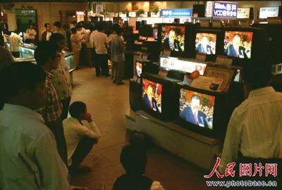 1997年9月12日。北京百货大楼。农民李小平蹲在彩电前看要闻现场直播。他很关心中央有什么新政策出台。