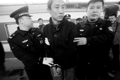 昨日上午,在哈尔滨参与绑架的吴某等3名犯罪嫌疑人被押解到沈阳北站。提起自己的女友,吴某流着眼泪,他的手上还文着女友的名字。 首席记者 徐刚 摄