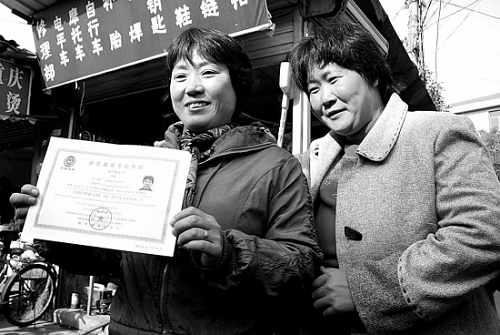 闫丽(左一)正向前来为她祝贺的邻居们展示刚刚拿到的全国英语三级证书。 陈未鸣 摄