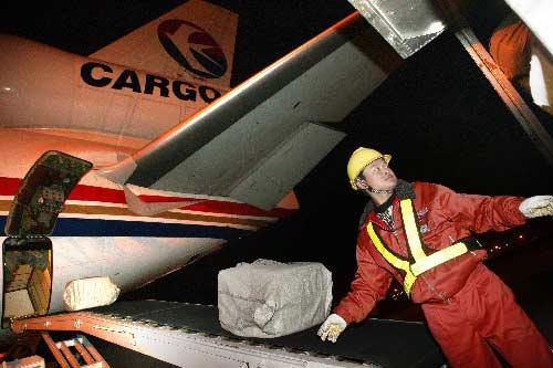 12月16日晚,一名浦东机场工作人员向CK261次班机机舱装载货物