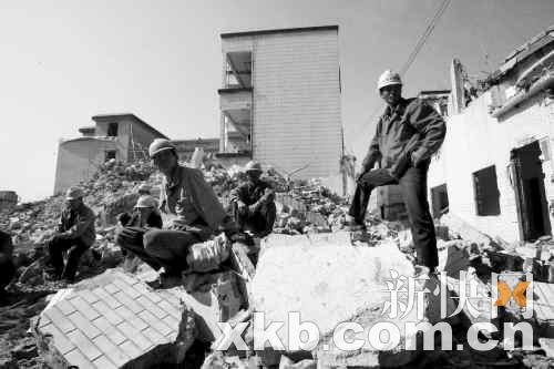 """昨日,拆迁工人站在工地上。因""""钉子户""""的阻拦,他们已经停工半个月。 李小萌/摄"""