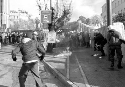12月18日,一名希腊示威者在雅典向警察投掷燃烧瓶。6日开始的骚乱至今仍未平息