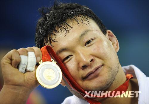 8月14日,蒙古国选手图布辛巴亚尔在领奖台上展示金牌。新华社记吴晓凌摄