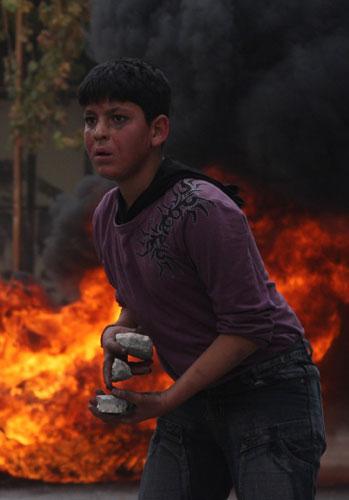 伯伦发生冲突抗议以军空袭 12月29日,在约旦河西岸城镇希伯伦,巴勒斯坦少年准备向以色列士兵投掷石块。当日,上百名巴勒斯坦人在希伯伦抗议以军空袭加沙地带,并与以色列士兵发生冲突。 新华社发(马蒙·沃兹摄)