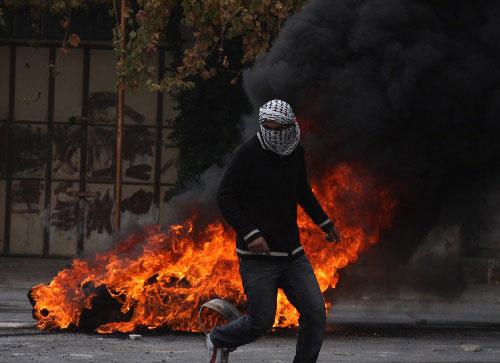 希伯伦发生冲突抗议以军空袭 12月29日,在约旦河西岸城镇希伯伦,巴勒斯坦少年准备向以色列士兵投掷石块。当日,上百名巴勒斯坦人在希伯伦抗议以军空袭加沙地带,并与以色列士兵发生冲突。 新华社发(马蒙·沃兹摄)