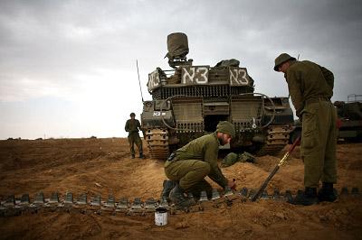 """28日,以色列士兵在加沙边境调试坦克。以色列国防部长巴拉克昨天声称考虑 """"扩大战争"""",目前以军正陈兵边境。 CFP"""