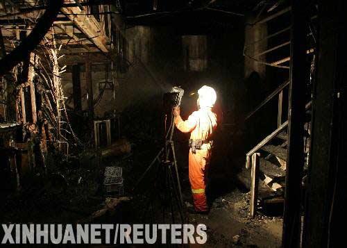 1月1日凌晨,一名消防员在泰国首都曼谷发生火灾的赛提卡夜总会里搜寻遇难者。