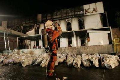 一名消防队员站在摆好的尸体旁边