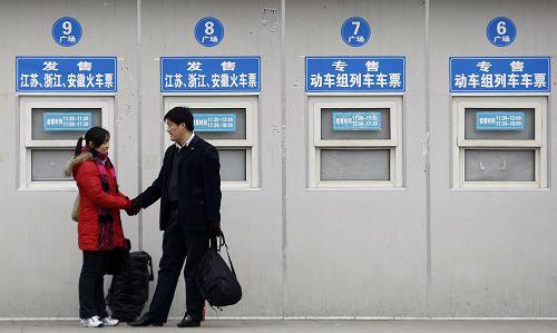 一对旅客等候在售票窗口前。早报记者 王炬亮