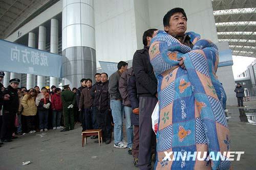 1月2日,在宁波国际会展中心临时售票点,一名排了两天队的购票者披着棉被等待买票。新华社发(张培坚 摄)