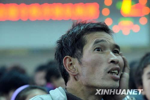 1月3日,一名接站的农民工正在查看列车到站时间表。
