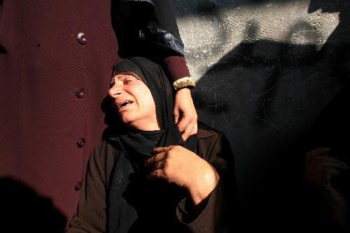 加沙遍是伤心地 1月5日,在加沙南部拉法难民营举行的哈马斯成员穆罕默德·阿布·沙尔的葬礼上,一名伤心的巴勒斯坦妇女无助地靠在亲友身边。 新华社发