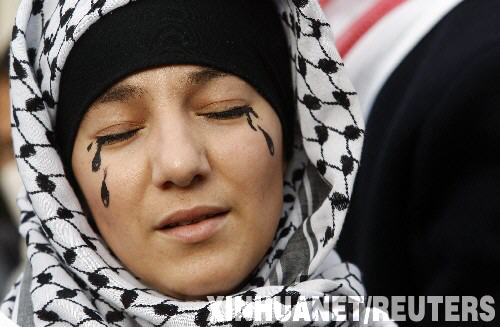 1月10日,在法国马赛举行的反战游行上,一名示威者在脸上画上黑色的眼泪。新华社/路透
