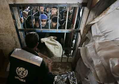 昨天,加沙的Shati难民营里的巴勒斯坦人聚集在联合国人道主义食品分配点前,焦急地等待领取粮食。 CFP图