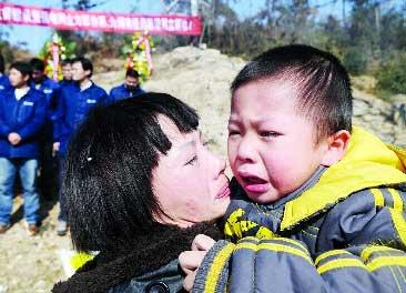 (长沙望城县桥驿镇,罗海文的妻子谢志红带着3岁的小儿子前来悼念)