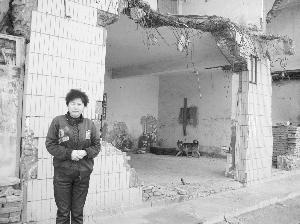 图为孙广凤站在曾是商店的露天房前
