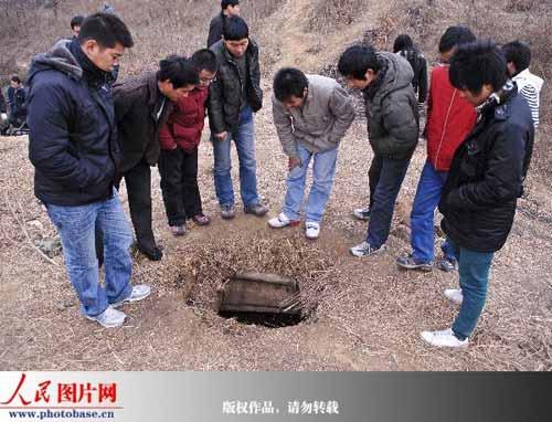 当地村民围观盗墓分子挖的盗墓通道洞口。