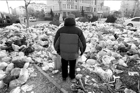 小区门口的道路上,垃圾成堆。 本报记者张沫摄