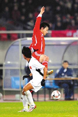1月21日,中国队球员郜林(上)在比赛中与越南队球员拼抢。